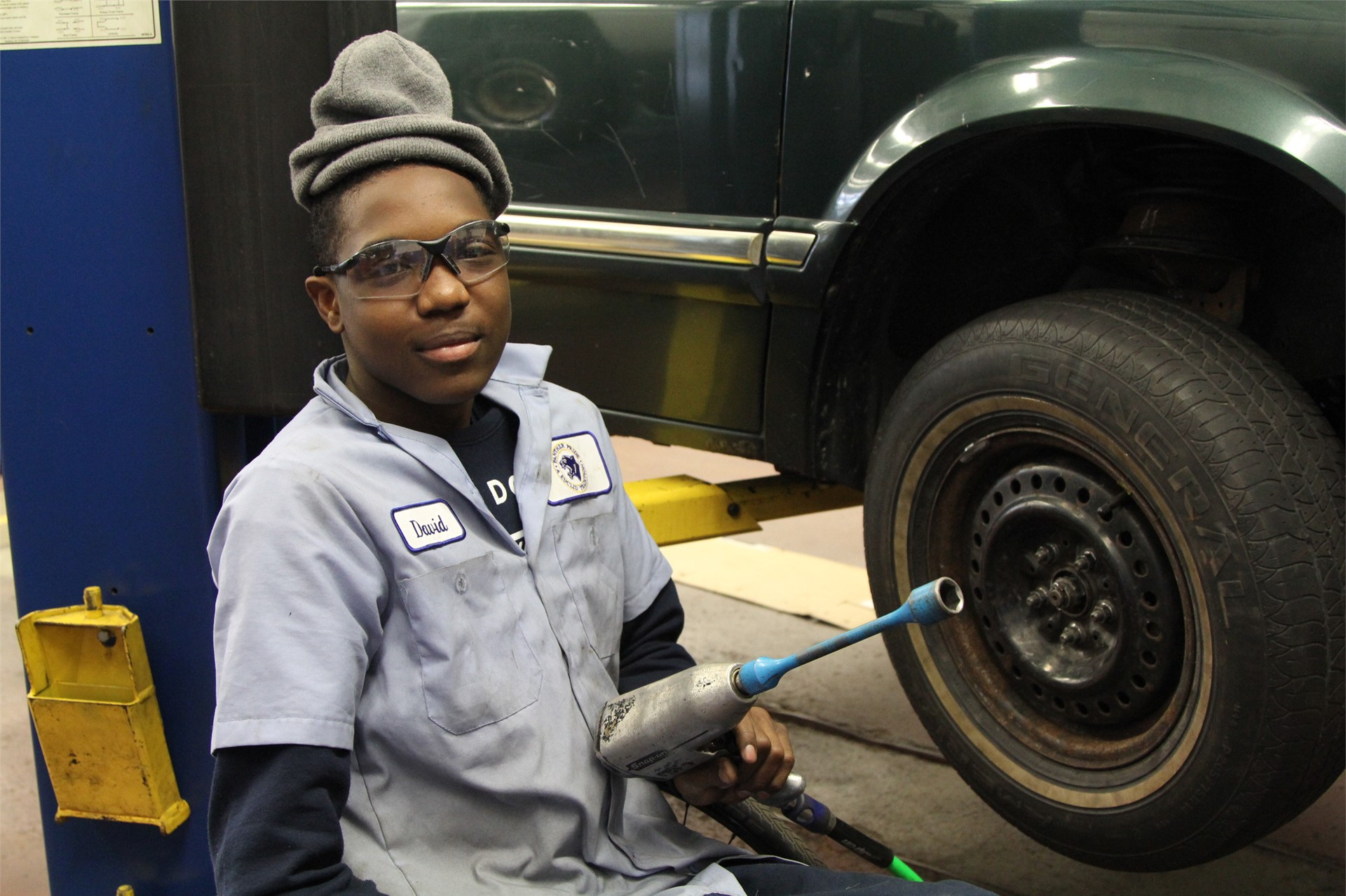Auto shop student replacing a tire